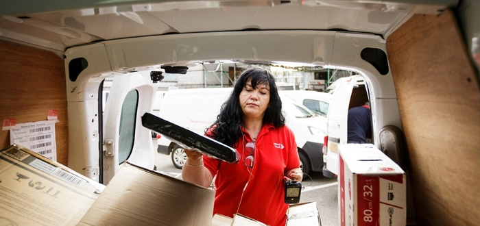 Image of a Jersey Post employee scanning parcels in the back of her van